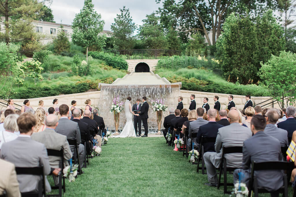an outdoor ceremony against the backdrop of the waterfall photo by brooke pavel photography - Greater Des Moines Botanical Garden