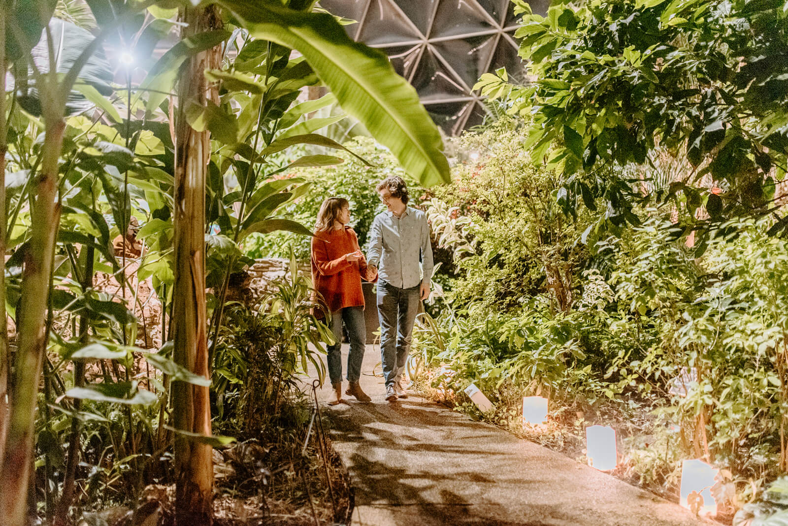 Two people walking in the Greater Des Moines Botanical Garden conservatory surrounded by tropical plants and lights.