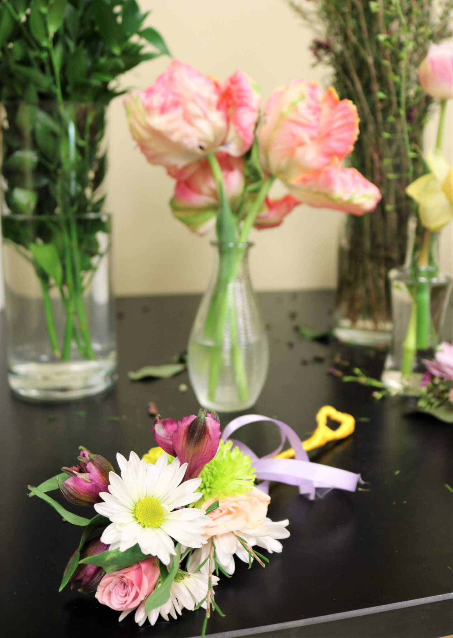 Small bundle of flowers laying on a black desk with vases of flowers in the background