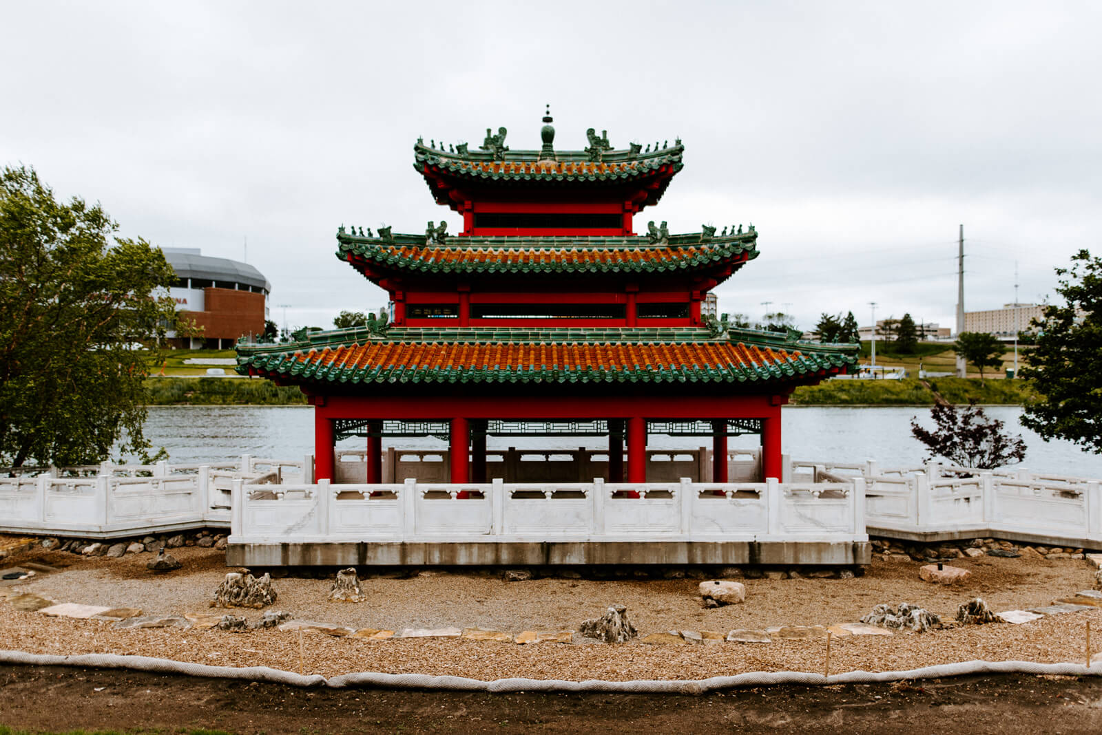 Red Asian pavilion in front of a river.